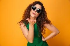 Поцелуи милой молодой женщины дуя нося солнечные очки Стоковое Изображение