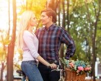 Поцелуй пар влюбленности на велосипеде и весна цветут парк корзины Стоковое Изображение RF
