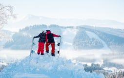 Поцелуй snowboarders пар na górze горы задний взгляд стоковые изображения rf
