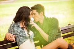 Поцелуи на скамейке в парке Стоковая Фотография