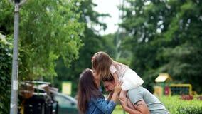 Поцелуи семьи Мама, папа и маленькая дочь идут вокруг парка города сток-видео