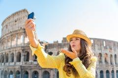 Поцелуи selfie женщины туристские принимая дуя на Риме Colosseum Стоковое Изображение RF