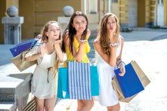Поцелуй 3 девушки держа хозяйственные сумки и прогулку вокруг магазина Стоковые Изображения