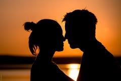 Поцелуй 2 людей на заходе солнца Стоковая Фотография RF