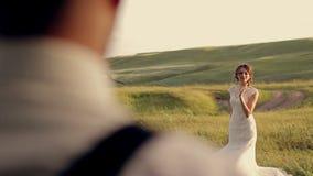Поцелуй groom невесты в парке на заходе солнца видеоматериал