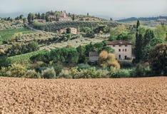Почва для виноградин местной фермы в ландшафте Тосканы с деревьями сада, особняками, зелеными холмами Итальянская сельская местно стоковое изображение
