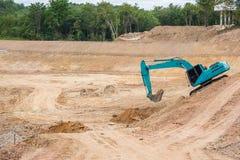 Почва и песок голубого backhoe копая экскаватором Стоковое Изображение RF