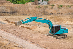Почва и песок голубого backhoe копая экскаватором Стоковая Фотография RF