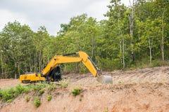 Почва и песок желтого backhoe копая экскаватором Стоковые Изображения RF
