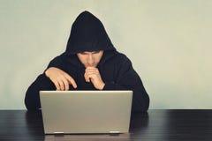 Почерните замаскированный хакер в черной длинной рубашке рукава сидит на столе перед компьтер-книжкой и думает что-то Он lookin Стоковое Изображение RF