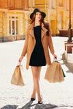 почерните покупку пятницы Привлекательная и жизнерадостная девушка идя город с покупками женщина ног принципиальной схемы мешка п Стоковое Фото
