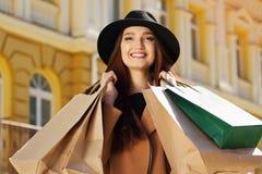 почерните покупку пятницы Привлекательная и жизнерадостная девушка идя город с покупками женщина ног принципиальной схемы мешка п Стоковые Изображения RF
