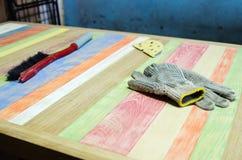 Почистьте щеткой и работая перчатки лежа на таблице от разных видов древесины в мастерской плотничества Стоковое Изображение RF
