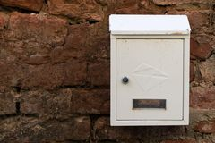 Почтовый ящик белого металла на кирпичной стене стена кирпича старая Почтовый ящик предусматриванный с пылью и грязью Стоковые Изображения