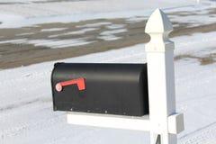 Почтовый ящик обозревает проезжую часть покрытую снегом Стоковые Изображения RF