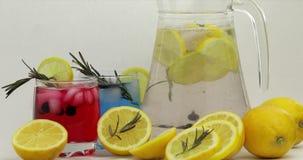 Пошевелите холодного напитка с лимоном, кубами льда и черной смородиной в стекле опарника видеоматериал