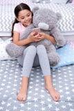 Пошлите сообщением сладостные мечты Ребенок девушки сидит на кровати с плюшевым медвежонком в ее спальне Ребенк подготавливает по стоковая фотография