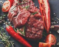 Пошутите над стейком, специями и овощами глаза на черной предпосылке Стоковое фото RF