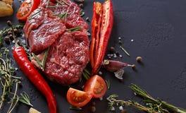 Пошутите над стейком, специями и овощами глаза на черной предпосылке Стоковые Фото