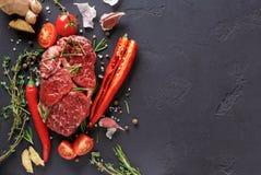 Пошутите над стейком, специями и овощами глаза на черной предпосылке Стоковая Фотография RF