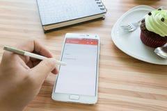 Пошлите электронную почту на телефоне в кофейне стоковая фотография
