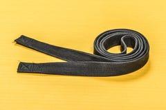 Пояс боевых искусств черный изолированный на желтой предпосылке циновки Стоковое Изображение RF