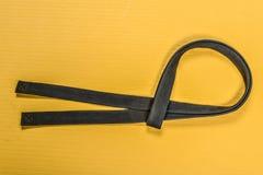 Пояс боевых искусств черный изолированный на желтой предпосылке циновки Стоковые Изображения