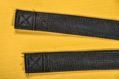 Пояс боевых искусств черный изолированный на желтой предпосылке циновки Стоковые Изображения RF