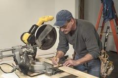 Пояс инструмента мужского плотника нося и использование квадратного инструмента для того чтобы отметить деревянную доску для реза Стоковые Изображения