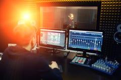Поя девушка поет к профессиональному микрофону в рекордной студии Процесс создает новое популарное песню молодой певицей стоковое фото rf