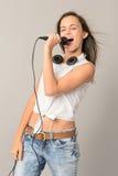 Поя девочка-подросток с глазами закрытыми микрофоном Стоковые Изображения
