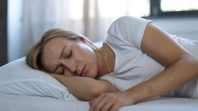 Подавленная женщина подпиранная вверх на подушке в кровати сток-видео