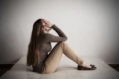 Подавленная женщина сидя на тюфяке Стоковые Фото
