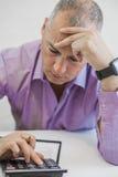Подавленный бизнесмен держа калькулятор Стоковые Фото