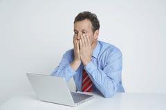 Подавленный бизнесмен смотря экран компьтер-книжки стоковое изображение rf