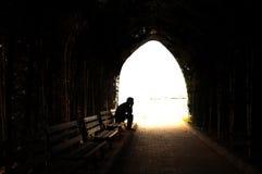 Подавленный молодой человек сидя на стенде Стоковая Фотография