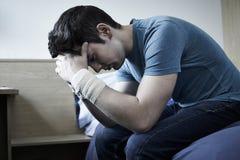 Подавленный молодой человек с перевязанными запястьями руки после попытки суицида стоковое изображение