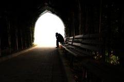 Подавленный человек сидя на стенде Стоковое Фото