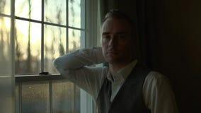 подавленный человек смотрит вне от темной комнаты сток-видео