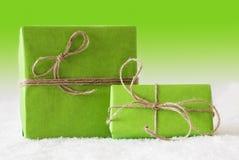 2 подарка на снеге, зеленой предпосылке Стоковая Фотография
