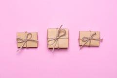 3 подарка обернутого в бумаге kraft на розовой предпосылке Взгляд сверху, плоский дизайн положения Стоковое Фото