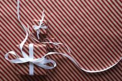 2 подарка с белой лентой на красной упаковочной бумаге Стоковая Фотография