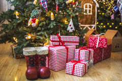 Подарки в красной и белой упаковке под зеленой рождественской елкой украшенной с игрушками и свечами рождества Стоковые Фотографии RF