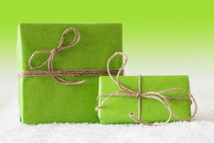 2 подарки или настоящего момента на снеге, зеленой предпосылке Стоковые Фото