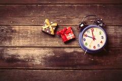 Подарки и часы на таблице Стоковые Изображения