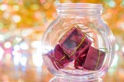 Подарки маленьких коробок в бутылке на предпосылке bokeh золота Стоковые Изображения
