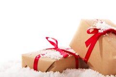 Подарки на рождество в коричневой бумаге с красной лентой Стоковые Фотографии RF