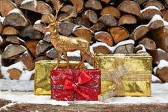 Подарки на рождество и figurine оленей перед woodpile Стоковая Фотография RF