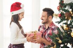 Подарки на рождество отца и дочери обменивая и раскрывая Стоковые Изображения RF