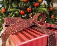 Подарки на рождество штабелированные вверх под рождественской елкой Стоковые Изображения